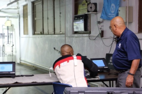 1SG Carrion assists a veteran Wounded Warrior at the Central Catholic Bordelon rifle range.